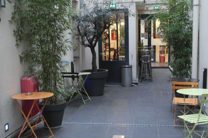 Innenhof des Loft Hostels in Paris mit bunten Sitzecken und vielen Pflanzen