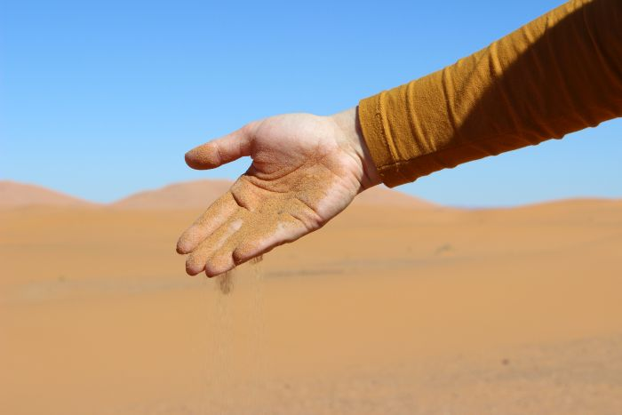 Eine Hand lässt den Sand der Sahara durch die Finger rinnen